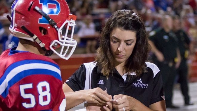 Crystal Evans, of the Andrews Institute, tends to a player during the football game at Pace High School on Friday, October 13, 2017.