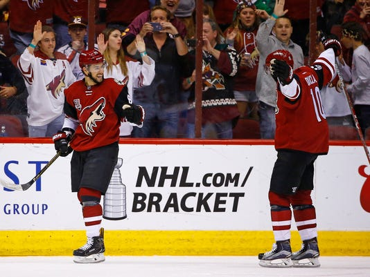Arizona Coyotes' Josh Jooris, left, celebrates his goal against the Washington Capitals with Anthony Duclair (10) during the first period of an NHL hockey game Friday, March 31, 2017, in Glendale, Ariz. (AP Photo/Ross D. Franklin)