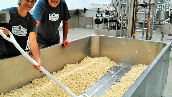 Dan and Debbie Takes stir cheese curds in a 463-gallon vat at their new creamery in Ely.  Whole milk from their dairy farm enters the vat, is slowly heated, then the whey is drained and curds are carefully cut, salted and raked – about a five-hour process.