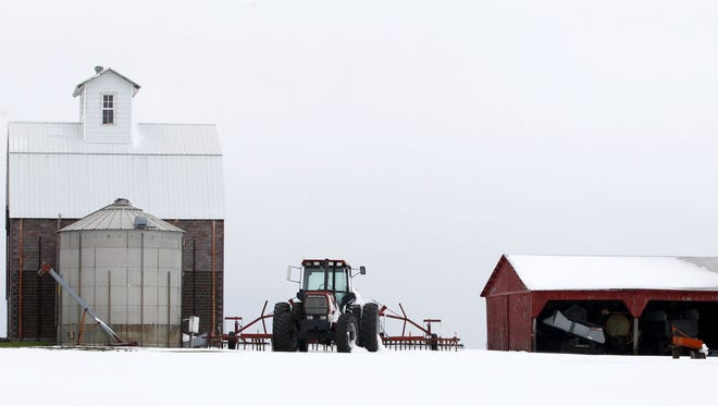 A tractor stands idle in the snow last year on a farm near Slater.