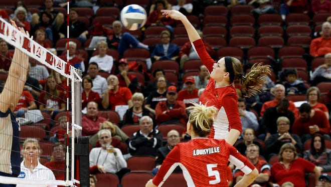 Louisville's Maggie DeJong smashes the ball over the net while teammate Katie George (5) looks on.  Nov. 6, 2015
