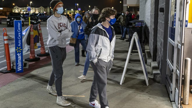 """""""I've never been first for any line in my life,"""" said Kai Deley, 16, center, as he along with his friend Sam Yoder, 16, left, were the first through the doors at 5 a.m. in search of a Sony Playstation 5 on Black Friday at the Walmart Supercenter on Freedom Drive, Friday, November 27, 2020, in Springfield, Ill. """"I didn't think we'd be this far up to be honest,"""" said Yoder about arriving to be the first in line about thirty minutes before the store opened."""