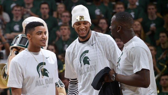 Michigan State basketball alumni, from left, Gary Harris, Adreian Payne and Draymond Green share a laugh at midcourt during a timeout Saturday at the Breslin Center.