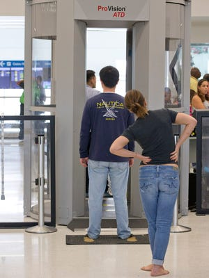 Passengers wait to pass through a full-body scanner as they go through security before boarding flights at the Fort Lauderdale-Hollywood International Airport on Dec. 18, 2015.