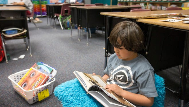 Christian Macias of Burk Elementary School reads his book in his classroom on March 31, 2015.