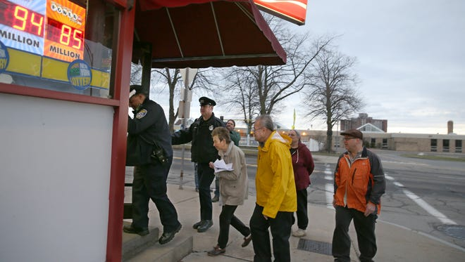 Rochester Police Department officers Anthony Belliard, left, and Brian Cannon, second from left, and neighbors from the South Avenue neighborhood near Charlotte Lahr's liquor store, led by organizer Geri Machado, third from left, head into Alice's Market on South Avenue as they walk door-to-door to show support for each other and pass along information, Tuesday, March 7, 2017.  A candlelight vigil will be held for Lahr outside her store Wednesday evening. Lahr was murdered in her store last week.