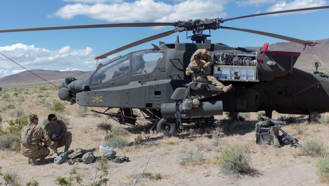Soldiers from Delta Troop, 3-6 Cav conduct a maintenance inspection on an Apache helicopter during the rotation at the National Training Center at Fort Irwin, Calif.