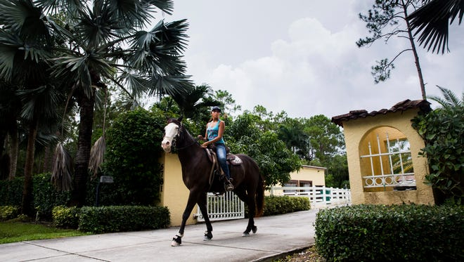 Rachel Caprio, 18, checks for traffic before riding her horse down the street outside her home in Naples on Friday, July 21, 2017. Caprio competes as a professional barrel racer in rodeos across Florida, Georgia and North Carolina.
