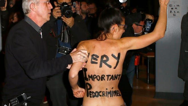 A Femen activist is led away by security staff member inside the film institute La Cinematheque Francaise in Paris, Monday, Oct. 30.