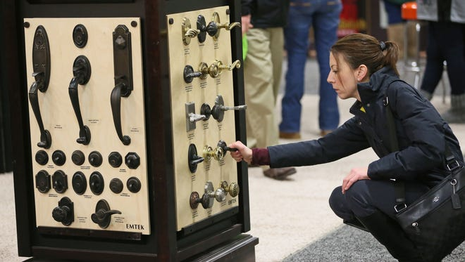 Jennifer Rakowski of Franklin looks over a display of door handles, knobs and latches at the 2016 MBA Home Building & Remodeling Show. The 2018 winter edition is this weekend at State Fair Park.