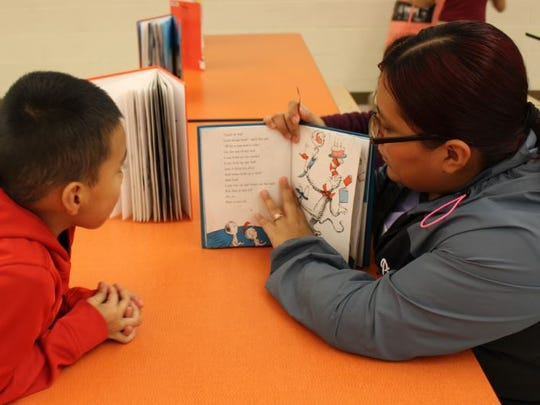 "Guadalupe Vaquero and her son Jorge Vaquero read a Dr. Seuss book during ""QML Loves to Read: Read Across America Night"" at Quarter Mile Lane School in Bridgeton."