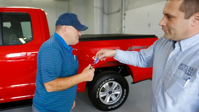Alton John, left, from Kittanning, Pa., gets the keys to his 2015 Ford F-150 Supercab 4x4 pickup truck from salesman Robert Myers in file photo. Car shoppers will find plentiful deals, relatively low interest rates and lots of high-tech choices in the market in 2017.