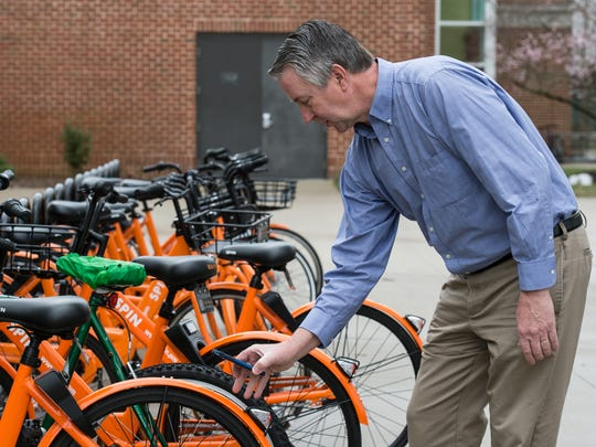 Wayne Shelton, SU's director of campus sustainability and environmental safety, demonstrates how to unlock a bike using the Spin smartphone application on Wednesday, Feb. 21, 2018.
