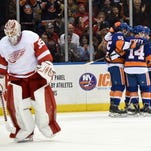 New York Islanders defenseman Johnny Boychuk (55), defenseman Johnny Boychuk (14), center Casey Cizikas (53) and right wing Cal Clutterbuck (15) celebrate Clutterbuck's goal as Detroit Red Wings goalie Jimmy Howard (35) skates away in the second period of an NHL hockey game on Sunday.