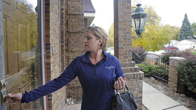 Melanie Hammer, freedom creator at Priceless Priorities, goes door to door handing out marketing materials for her business in Sioux Falls, SD; Tuesday, Oct. 20, 2015.