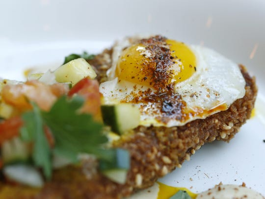 A sunny-side up quail egg lends protein to the eggplant