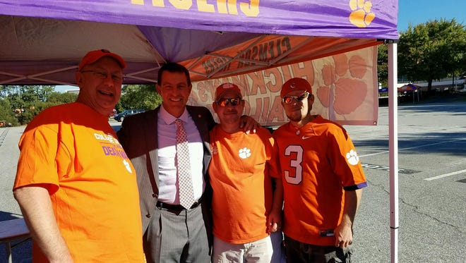 Clemson head coach Dabo Swinney poses for a photo with Clemson fans from left, Eddie Hickman, Swinney, Chris Hickman, and Aaron Roef on Saturday, October 1, 2016 in Clemson. Swinney stopped by the fans tailgate on Saturday morning on his way back to the team hotel in Anderson.