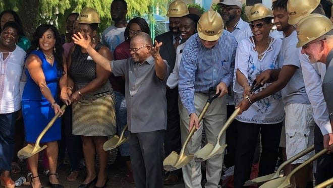Quality Life Center Executive Director Abdul'Haq Muhammed orchestrates a ceremonial ground breaking with community leaders at the Quality Life Center on Friday morning.