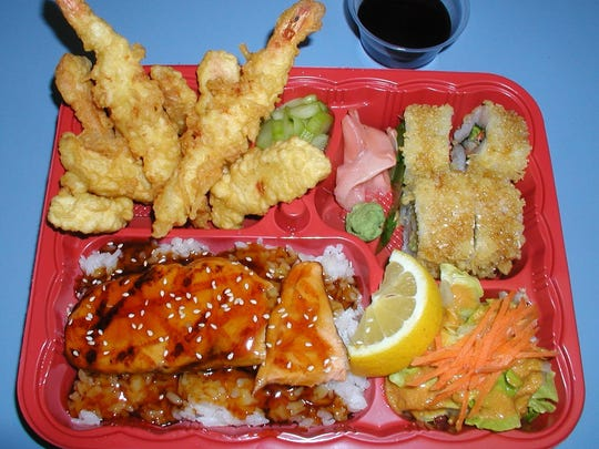 Bento box, clockwise from upper left: shrimp and vegetable tempura, marinated cucumbers, four pieces of crunchy roll, salad and grilled salmon on a bed of rice and covered in home made teriyaki sauce.