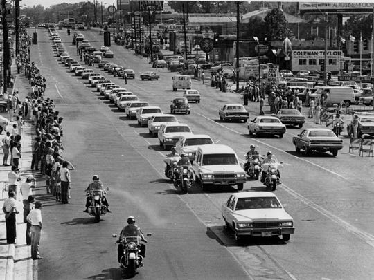 In this Aug. 18, 1977 file photo, a string of white vehicles follow the hearse carrying the body of Elvis Presley along Elvis Presley Boulevard on the way to Forest Hills Cemetery in Memphis, Tenn. Presley died at Graceland in Memphis on Aug. 16, 1977. The crowds in the aftermath got so thick that then President Jimmy Carter called out 300 National Guard troops to manage things.