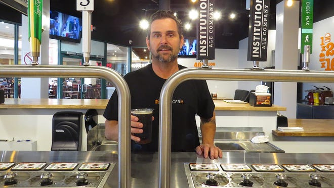 "Michael Nunes, owner of Burgerim at the Camarillo Premium Outlets, poses with the restaurant's Bottoms Up draft-beer system. ""People are just really enjoying sitting at the counter and watching the system in action,"" Nunes said."