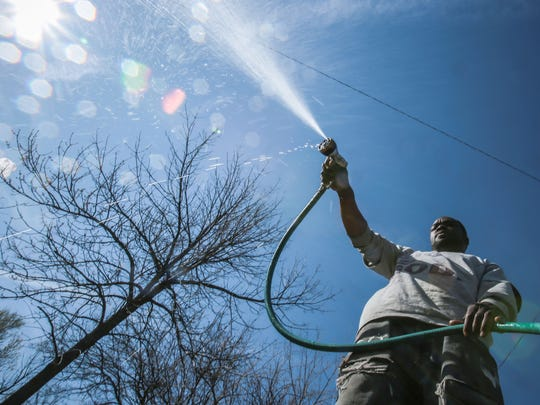 Erik Pritchett, 38, of Detroit, washes a car at the