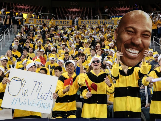 Michigan fans hold a sign of #WeWantSHEA, a picture of LaVar Ball, and Chinese flags before a basketball game against UCLA at the Crisler Center in Ann Arbor, Saturday, December 9, 2017.
