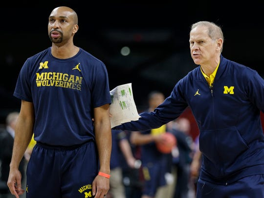 Michigan head coach John Beilein, right, talks to assistant