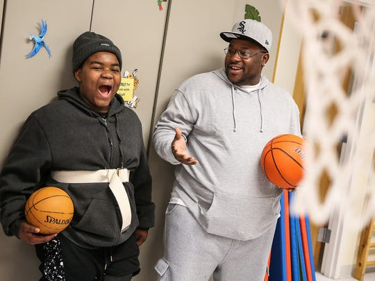 From left, Ty-Juan Preer, 11, and his father Ty-Juan, tease each other during a basketball shoot-out as part of his physical therapy session at Riley Children's Hospital in Indianapolis, Friday, March 30, 2018. Three years ago, Ty-Juan Jr. was hit and paralyzed in a drive-by shooting. He is walking again with the help of braces and a walker and has set a goal to play football again.