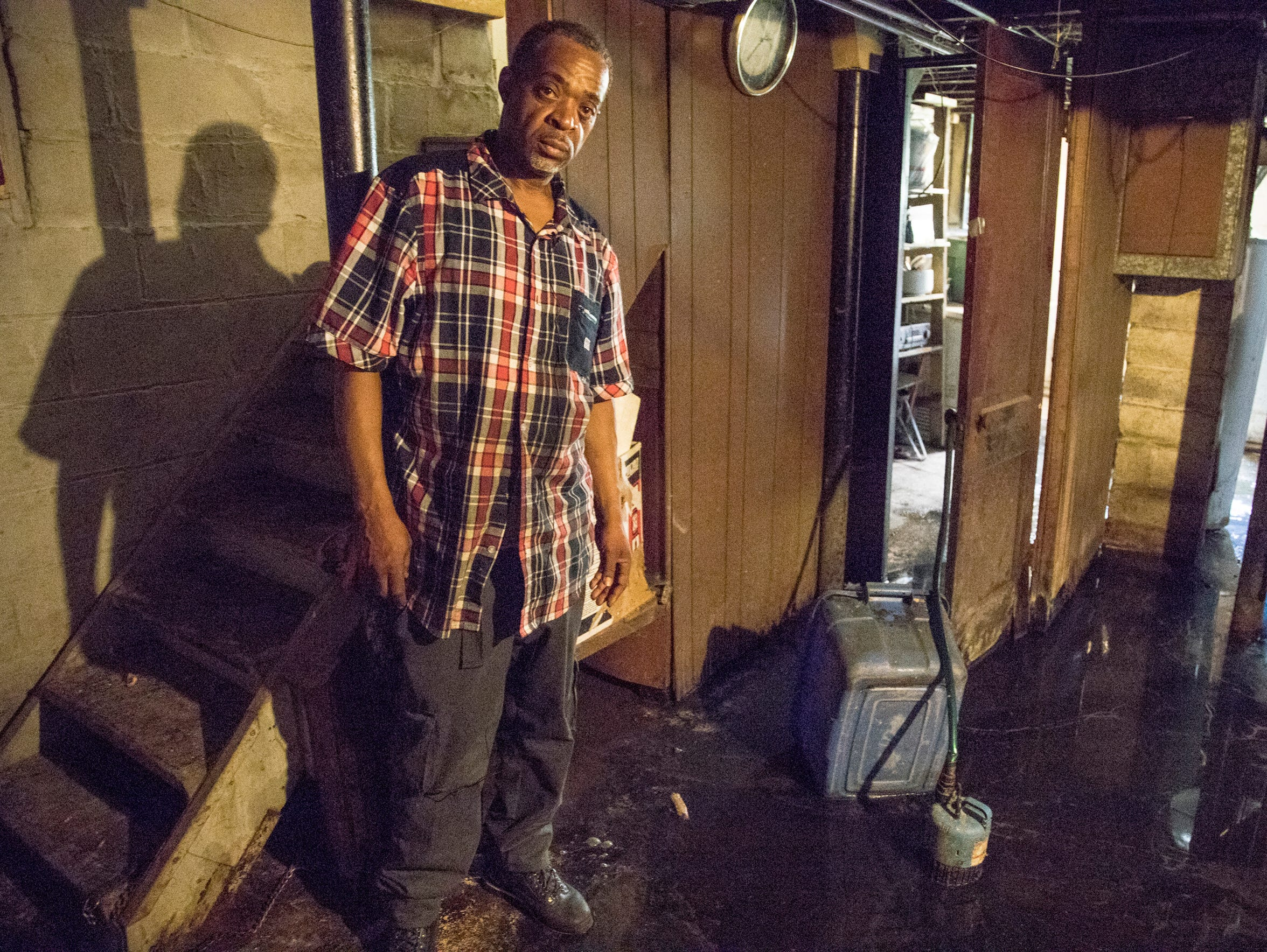 William Love poses in May for a photo in the flooded basement of the house on Hull Street in Detroit that he is purchasing from the land bank. (Photo taken May 31, 2018)