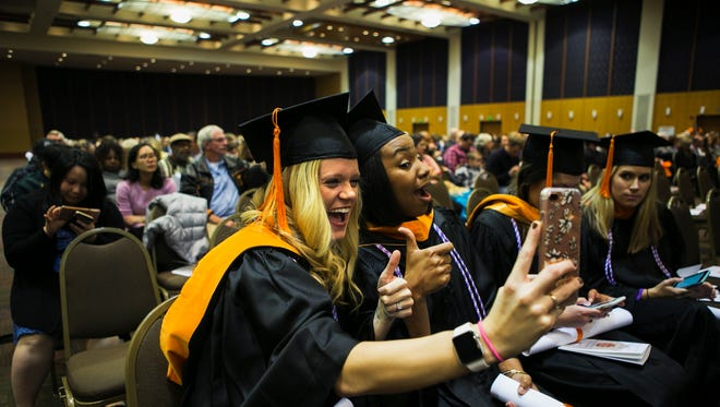 Nursing graduates Lindsey Webber, left, and Amanda Whaley strike a pose for a selfie in their caps and gowns during University of Tennessee Health Science Center's graduation at the Cook Convention Center last December. UTHSC graduated 135 new health care professionals during its winter commencement.