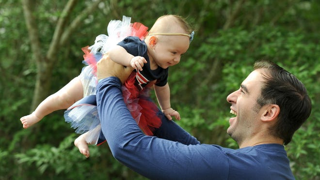 Proud father Chris Flanagan holds his daughter, Aubrey, high in the air. Aubrey was born Feb. 1,  just as the coronavirus was starting to emerge across the country.