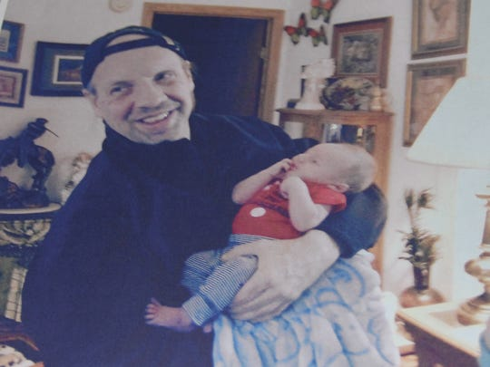 Bradley Goad, 45, holds his first grandson, Brilyn. He turned one a few days after Brad died.