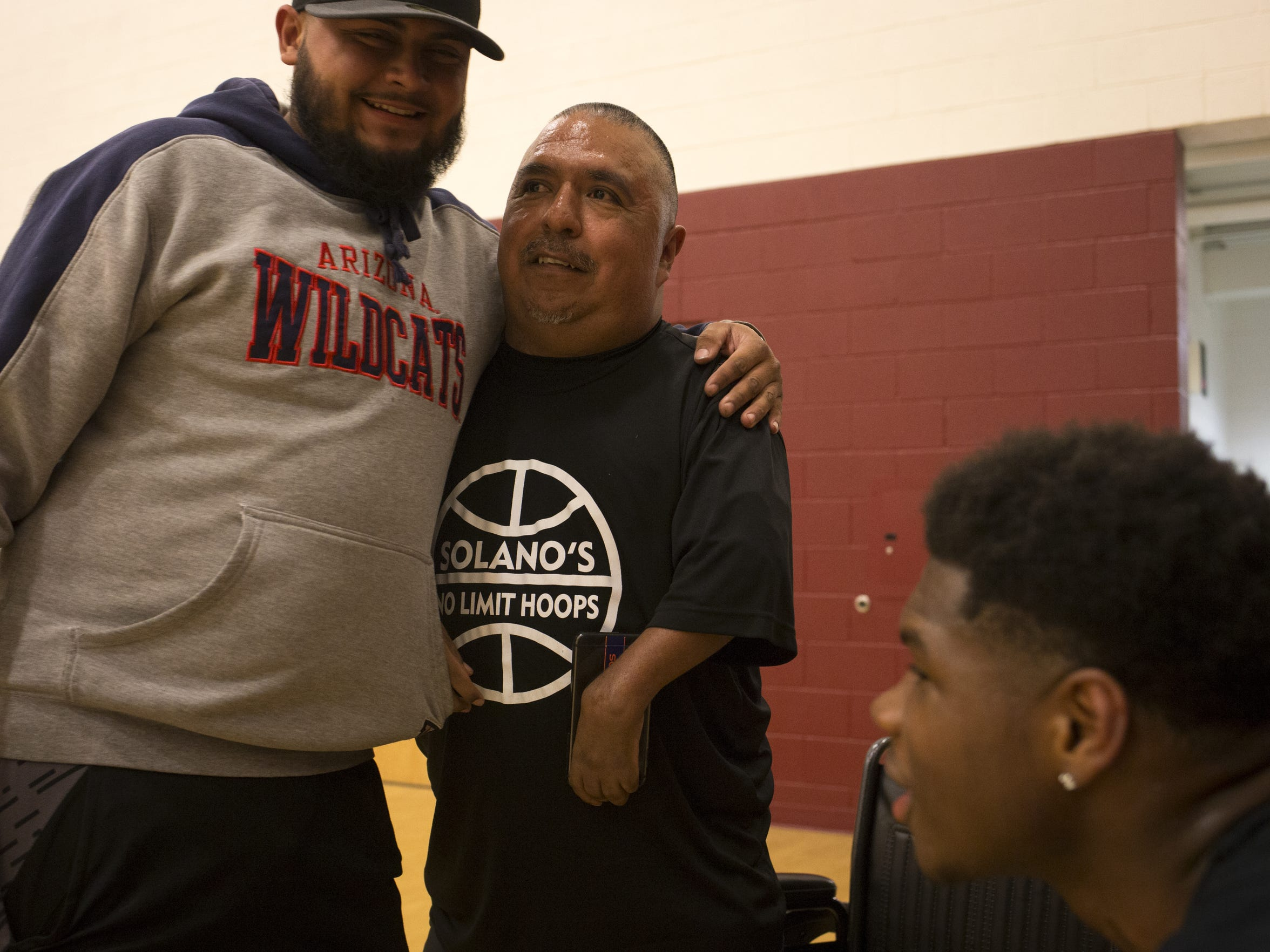 David Solano, center, talks with Wilver Calderon, left, during Solano's No Limit Hoops in February.