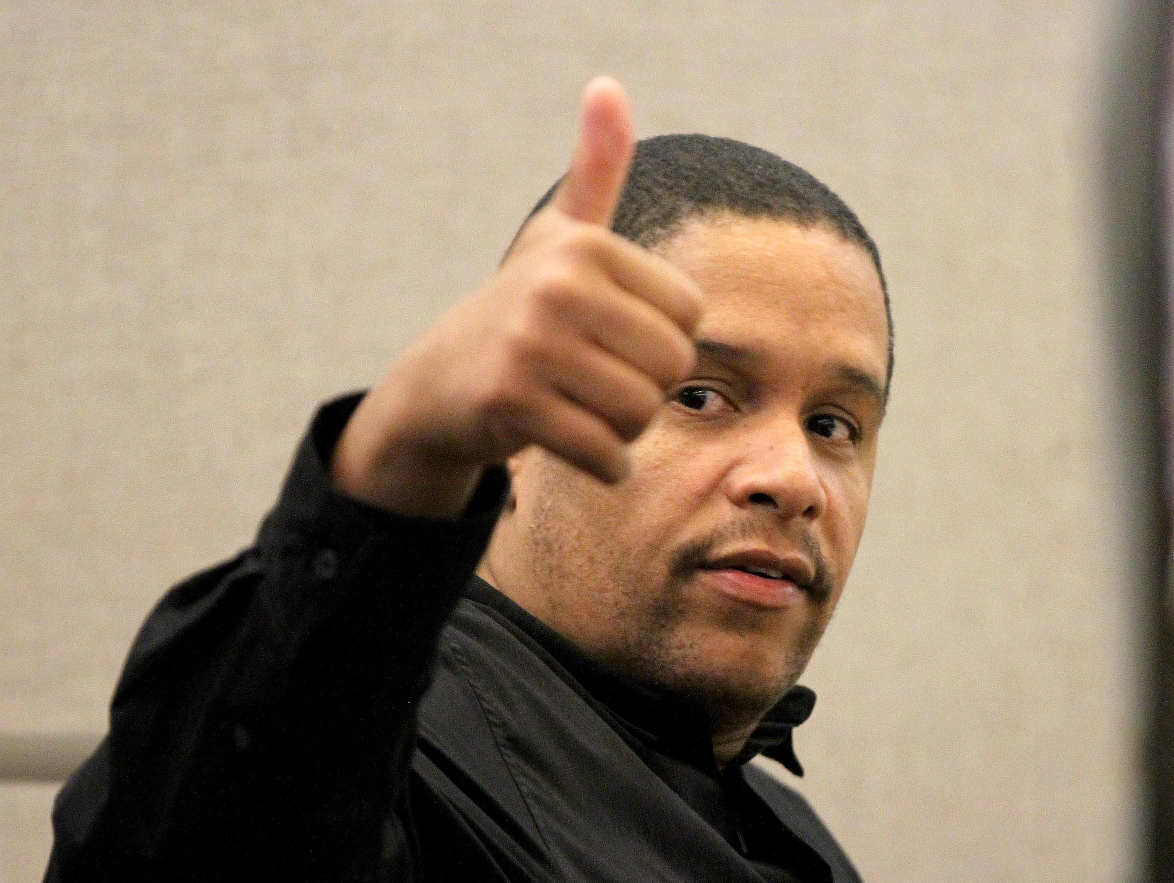 Keith German, the former Asbury Park police officer who went on the lam while on trial with two alleged gang members, flashes a thumbs-up to women in the gallery before his trial resumed at the Monmouth County Courthouse.