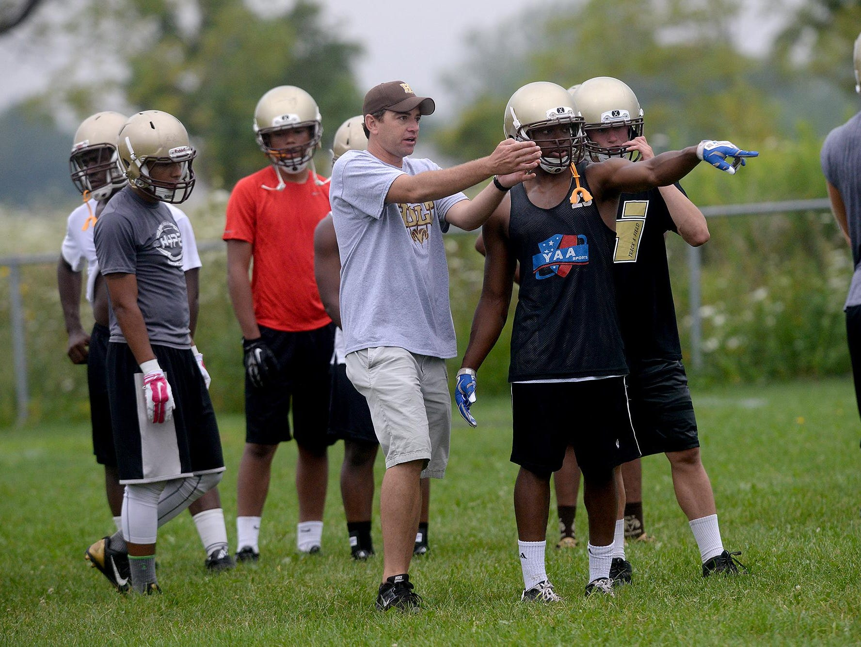 Head Coach Chad Fulk goes over a play with a running back Monday, August 10, 2015,l during drills on the first day of practice for the Rams. Fulk, a 1995 graduate of Holt, is in his first year as head coach of the Rams.