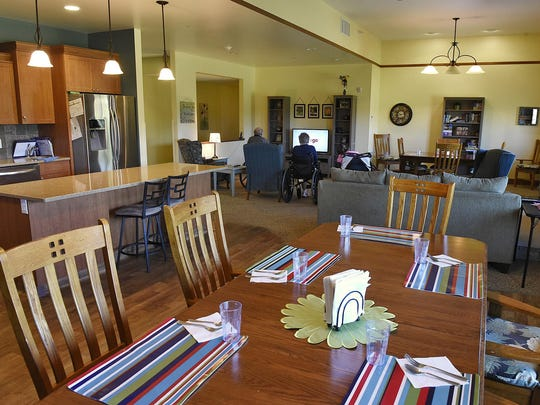 Residents watch television in the living room next to the large kitchen and dining area Tuesday at Cherrywood Advanced Living