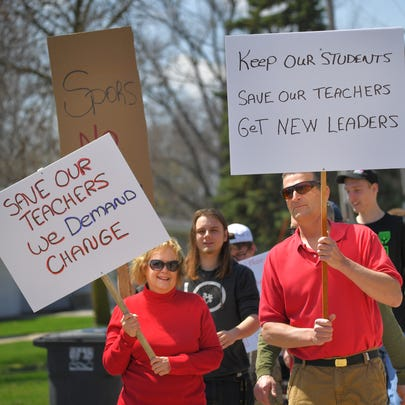Student and parents march with protest signs against