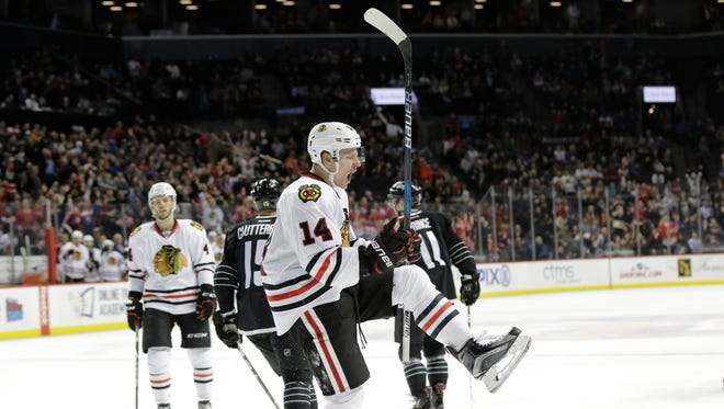 Chicago Blackhawks' Richard Panik (14) celebrates after scoring a goal as New York Islanders' Shane Prince (11) and Cal Clutterbuck (15) skate away during the third period of an NHL hockey game Thursday, Dec. 15, 2016, in New York. The Blackhawks won 5-4.