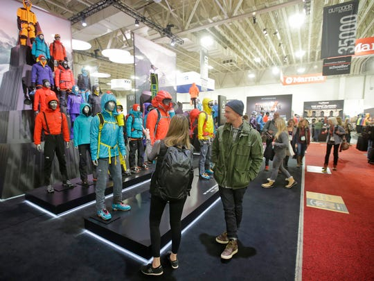 In this Wednesday, Jan. 11, 2017, photo, people attend the Outdoor Retailer show at the Salt Palace Convention Center in Salt Lake City. Footwear's position as the second largest segment within the lucrative outdoor retail industry is on full display at a trade expo in Salt Lake City this week with a wide array of colorful sandals, shoes and boots that companies promise are lighter and can be used for more activities.