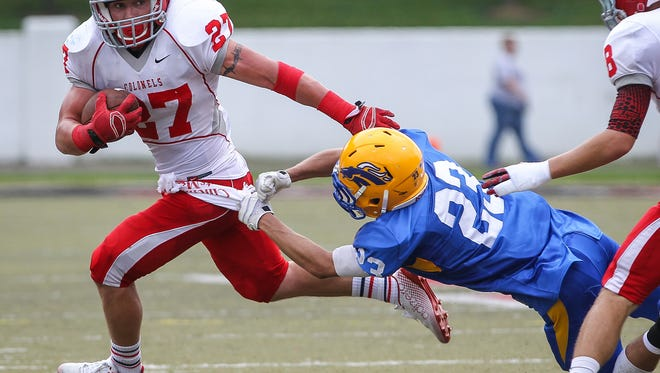 Dixie's Luke Zajac runs away from NewCath's Nate Enslen during the second quarter.