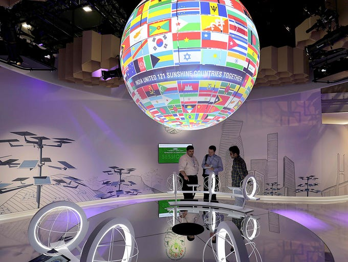 Visitors stand beneath a spinning Globe with the flags