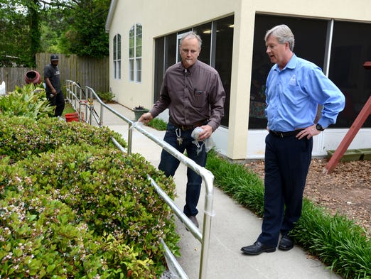 Jeff Nall, Vice President/Communication and Development for Council on Aging of West Florida, right, chats with Kevin Marchetti, the owner of Renaissance Man Inc., as a new hand rail is installed Thursday as part of an Impact 100 grant to the organization.