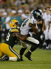 Green Bay Packers linebacker Sam Barrington (58) tries to bring down Philadelphia Eagles running back Ryan Mathews (24) in the second quarter during Saturday night's preseason game at Lambeau Field.
