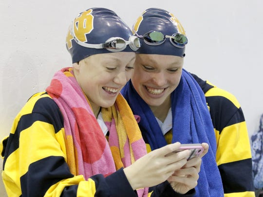 Molly Craig (left) and Frances VanderMeer checking out a selfie they took after training at the Ernie Davis Academy pool in 2015, when they were Elmira Notre Dame teammates.