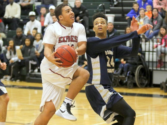 Elmira's DeShaun Sutton drives to the basket while guarded by James Williams of Bishop McDevitt during Tuesday's National Consolation game at the Josh Palmer Tourney.