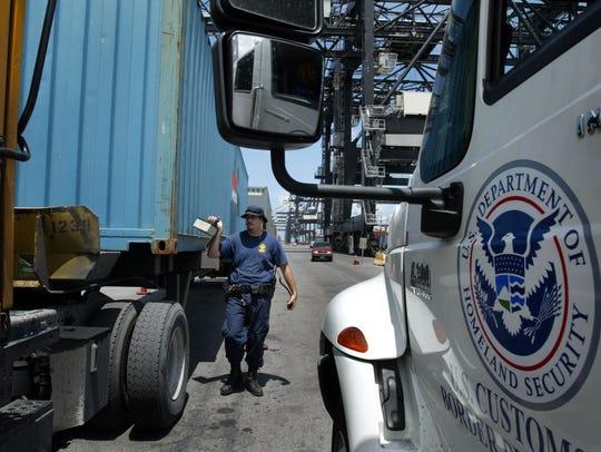 Un agente del CBP inspecciona unos camiones en la garita.