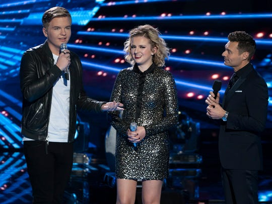 """Maddie Poppe (center) of Clarskville, Iowa, looks on as fellow finalist Caleb Lee Hutchinson (left) reveals the two are dating Monday, May 21, 2018, during the """"American Idol"""" finale in Los Angeles."""