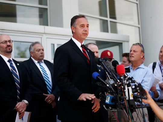 Anne Arundel County state's attorney Wes Adams, center,