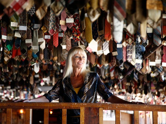 Marketing manager Lisa Cyr on April 29, 2014, stands under thousands ties that were cut off the necks of overdressed Pinnacle Peak Patio patrons over the years.